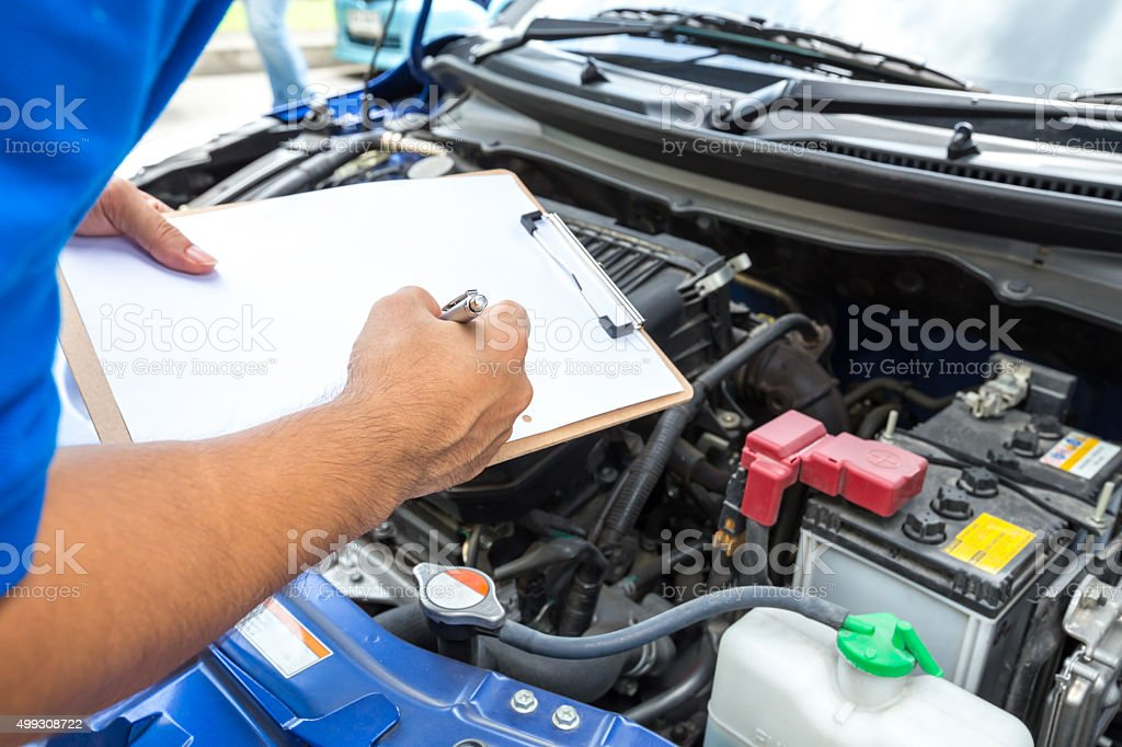 Mechanic man holding clipboard and check the car stock photo