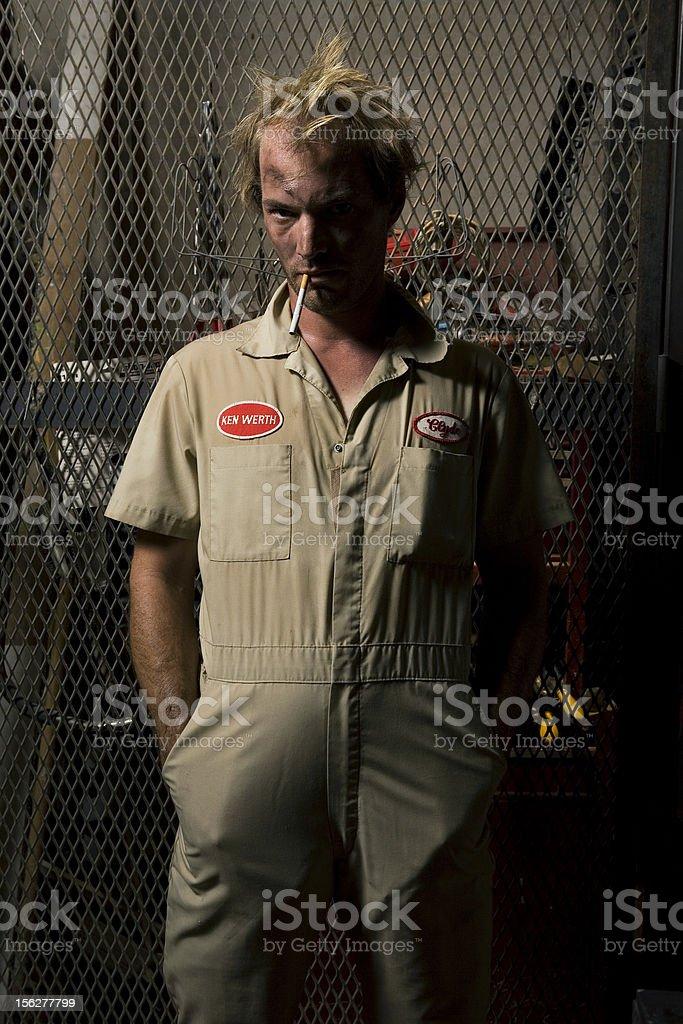 Mechanic Man Wearing Coveralls and Smoking Cigarette stock photo