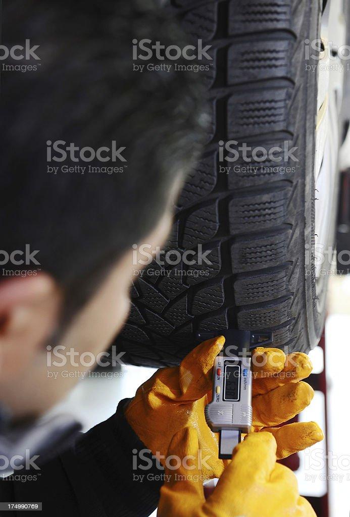 Mechanic measure tire tread depth royalty-free stock photo