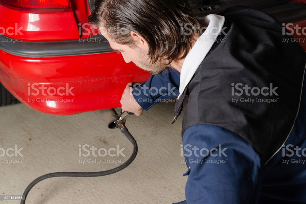 Mechanic measuring exhausts of a car in garage stock photo