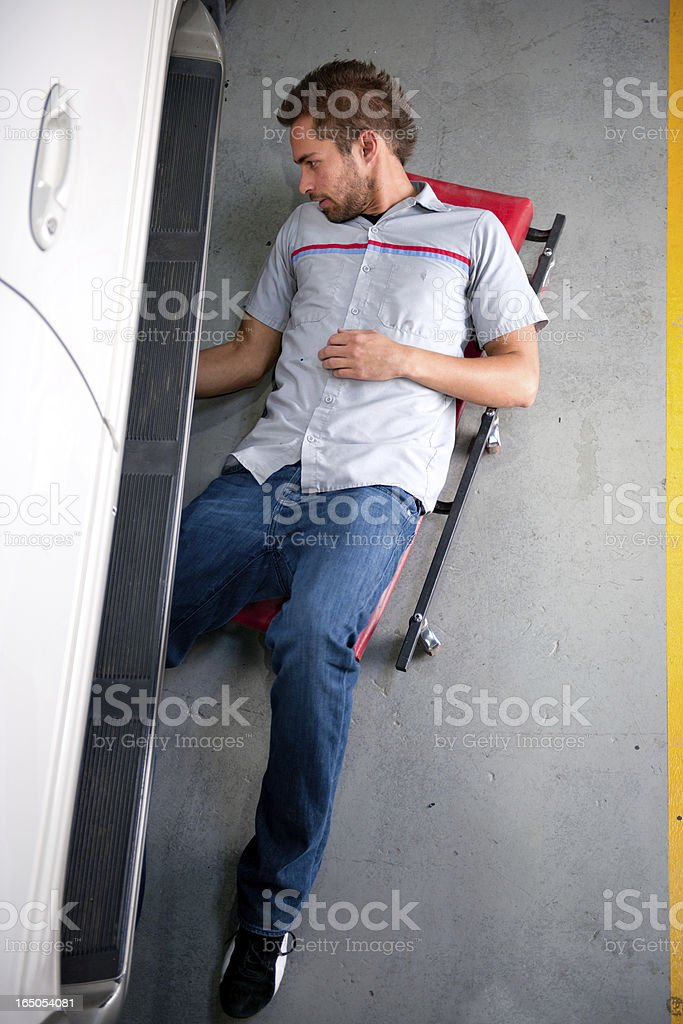 Mechanic On Dolly Rolling Under SUV stock photo
