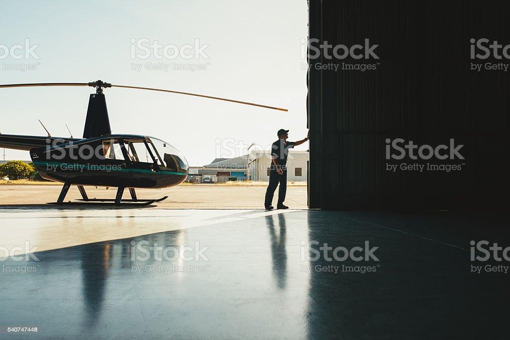 Mechanic opening the door of a airplane hangar stock photo