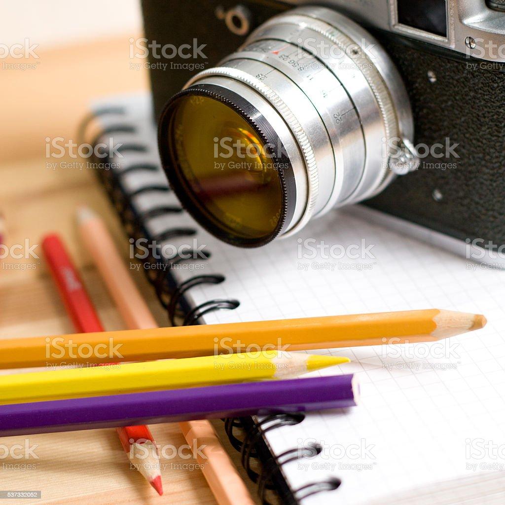 Mechanic photo camera, pencils and a notebook stock photo
