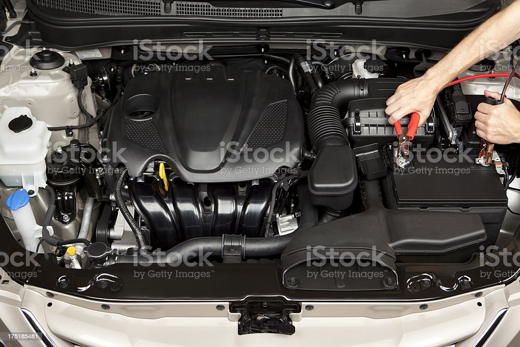 Mechanic Placing Jumper Cables on a Battery stock photo
