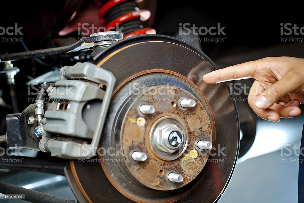 mechanic pointing at brake rotor stock photo