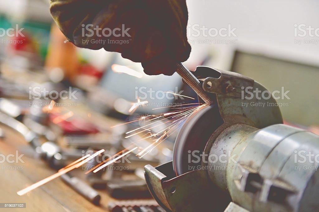Mechanic polishing a screw on industrial polishing machine stock photo