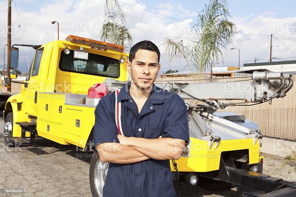 Mechanic posing next to tow truck stock photo