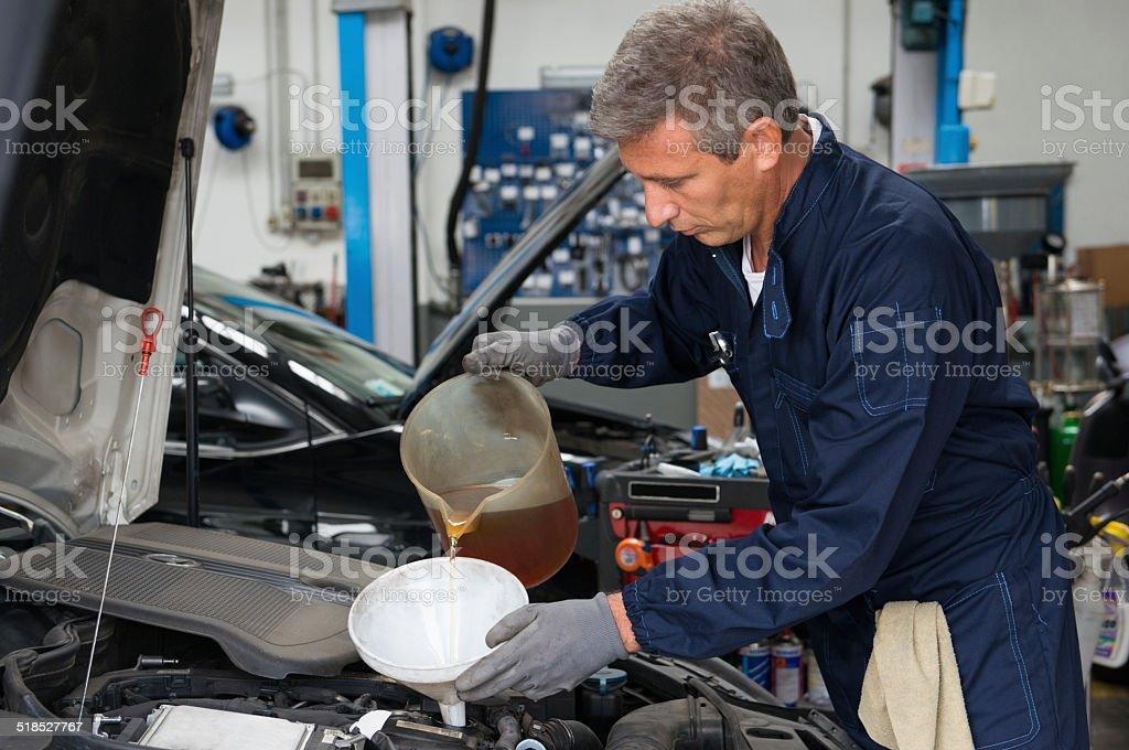 Mechanic Pouring Oil In Car Engine stock photo