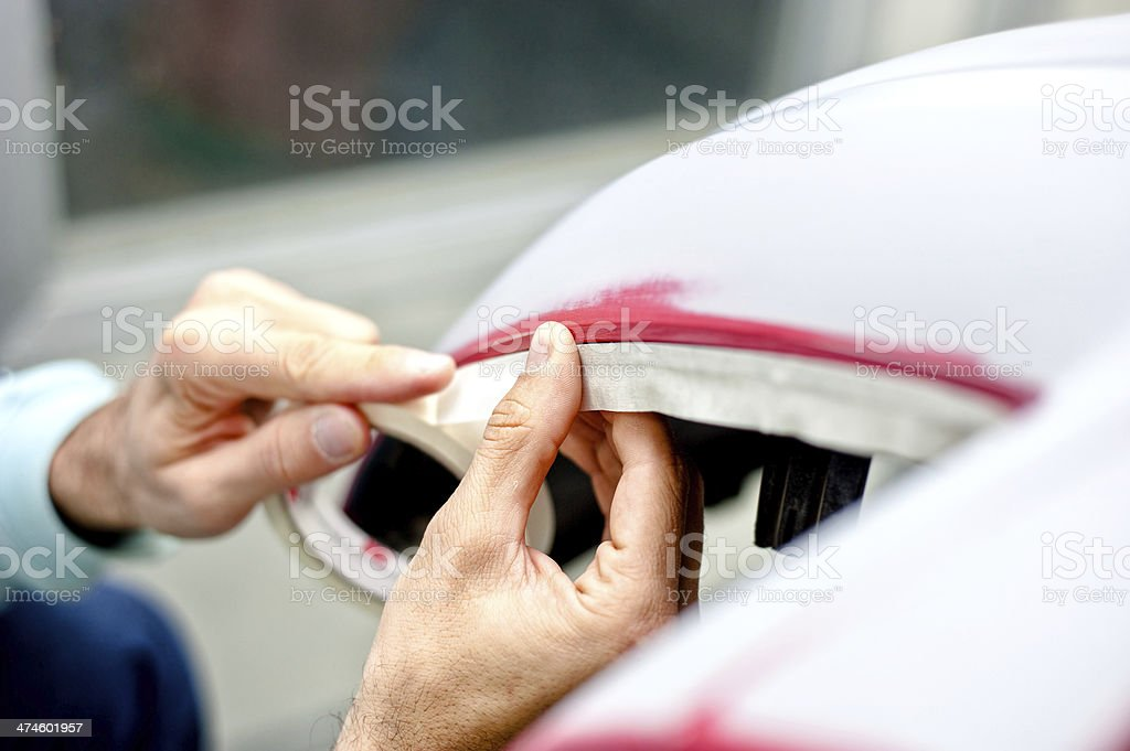 Mechanic preparing a car for painting by protecting the edges stock photo