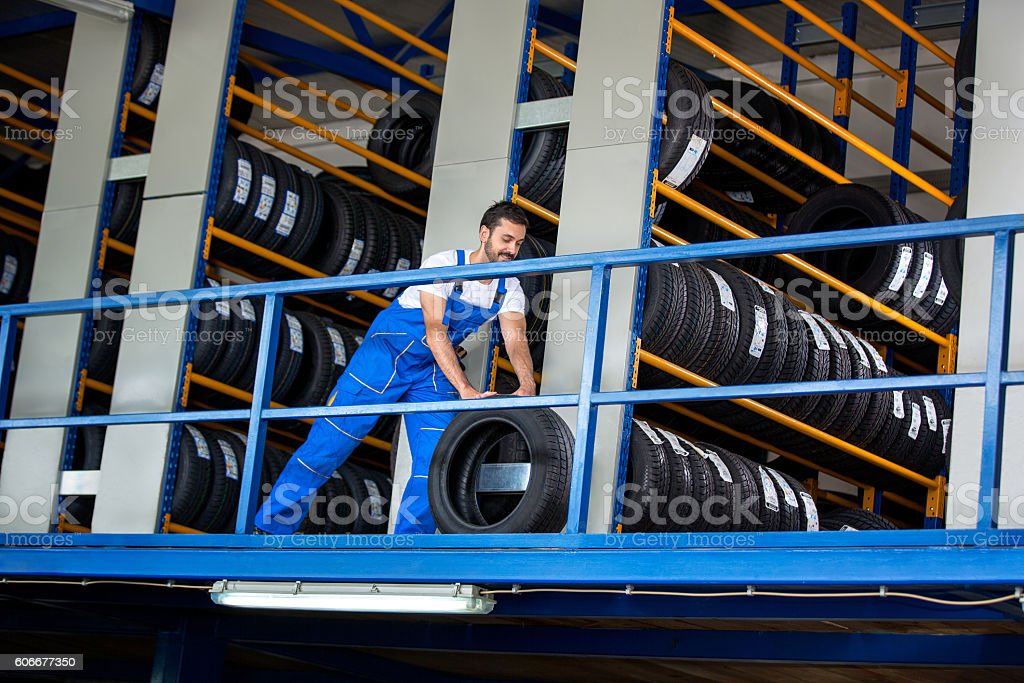 Mechanic pushes the car tire stock photo