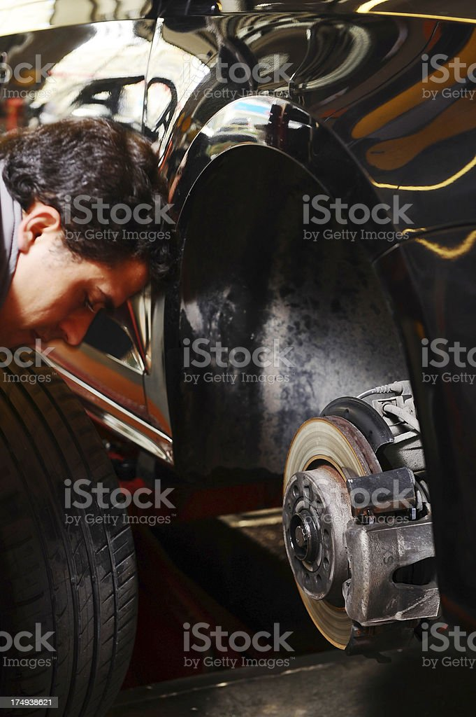 Mechanic puts the tire back onto a car royalty-free stock photo