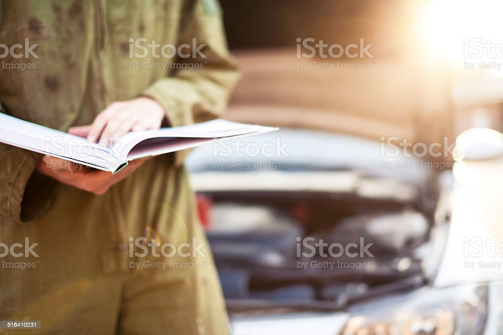 Mechanic reading instructions under open hood stock photo