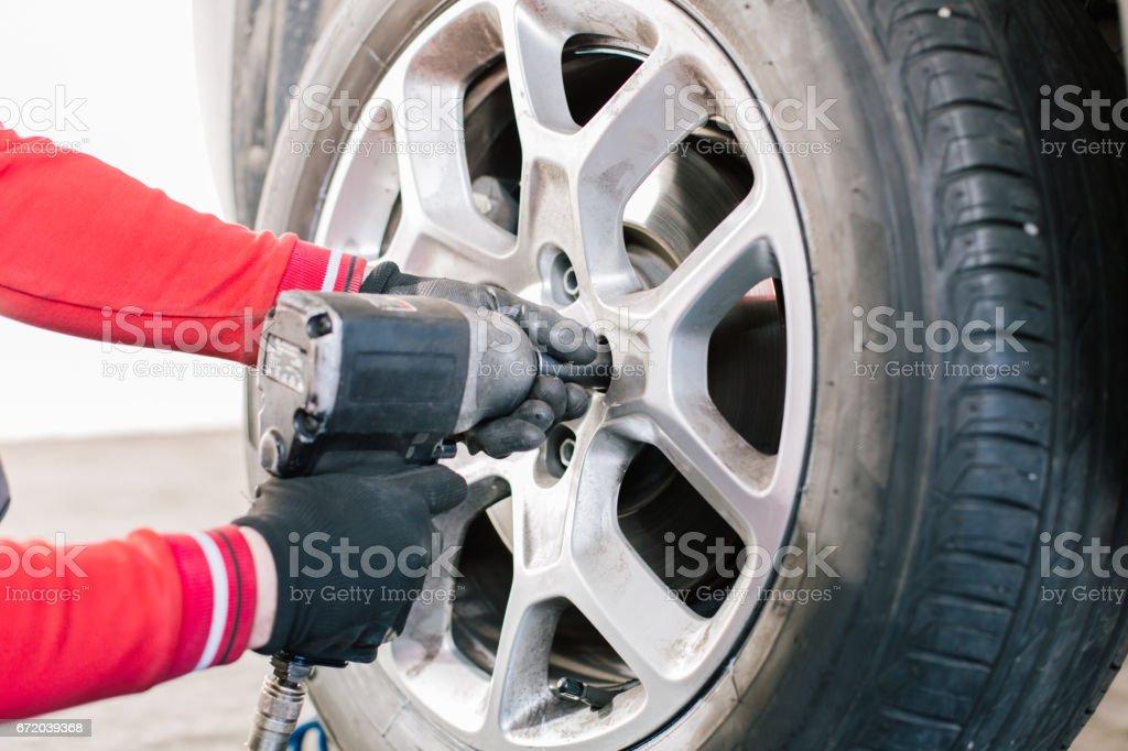 Mechanic removes car tire closeup stock photo