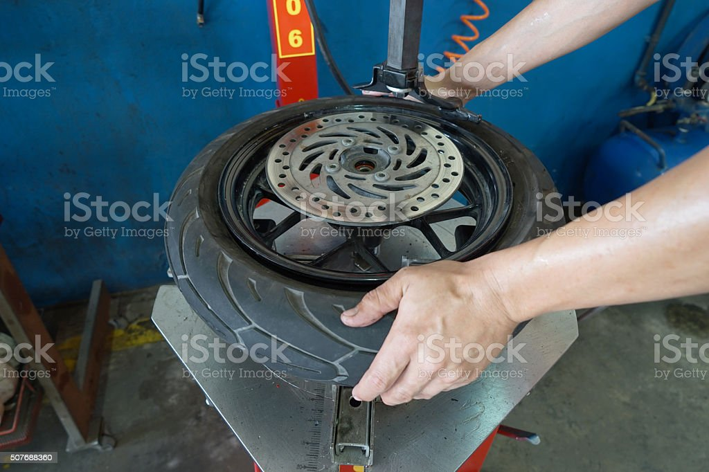 Mechanic removes tire closeup stock photo