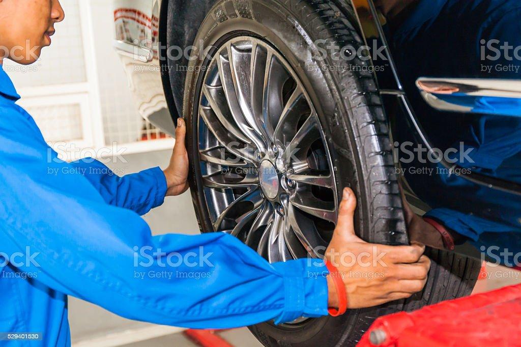 mechanic removing or replacing car wheel at car service garage stock photo