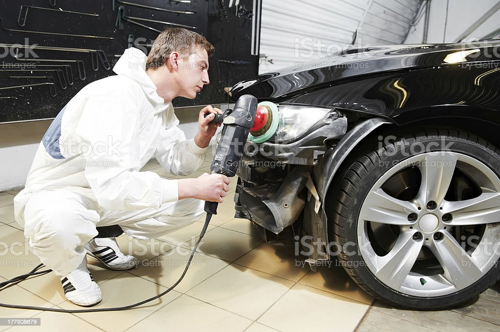 mechanic repairing and polishing car headlight royalty-free stock photo
