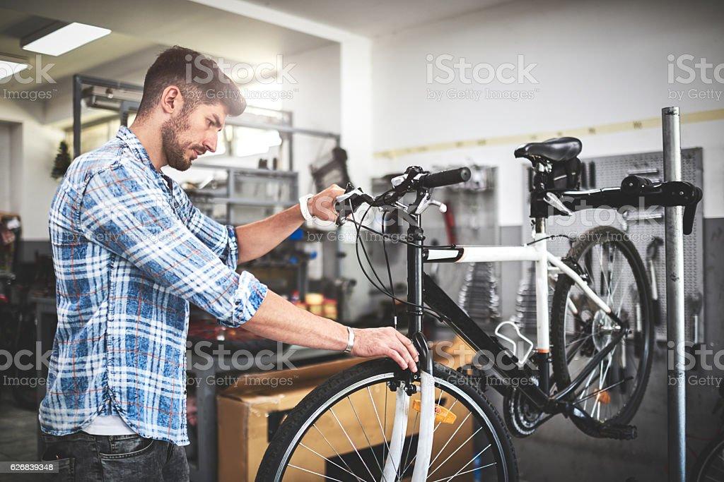 Mechanic repairing bicycle stock photo