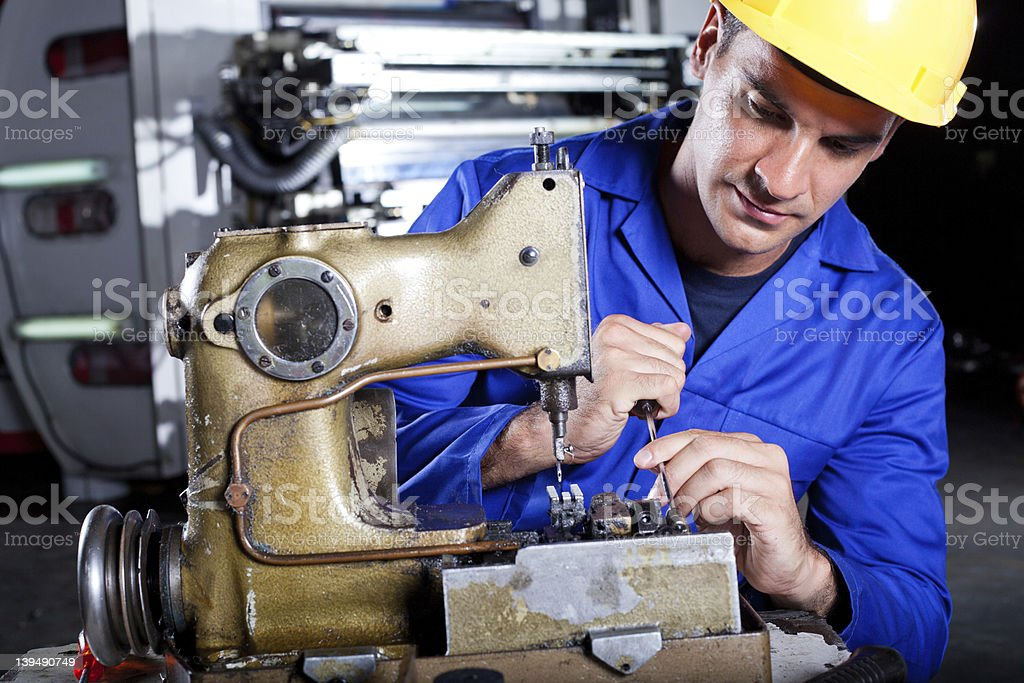 mechanic repairing industrial sewing machine royalty-free stock photo