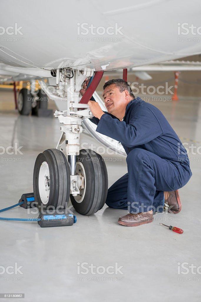 Mechanic repairing landing gear of an airplane stock photo