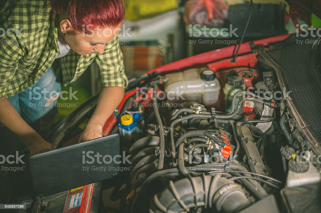 Mechanic repairing the motor or electric parts of a car stock photo