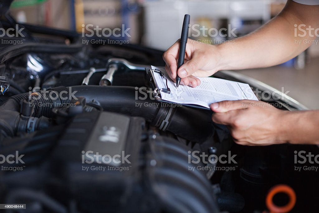 mechanic repairman inspecting car stock photo
