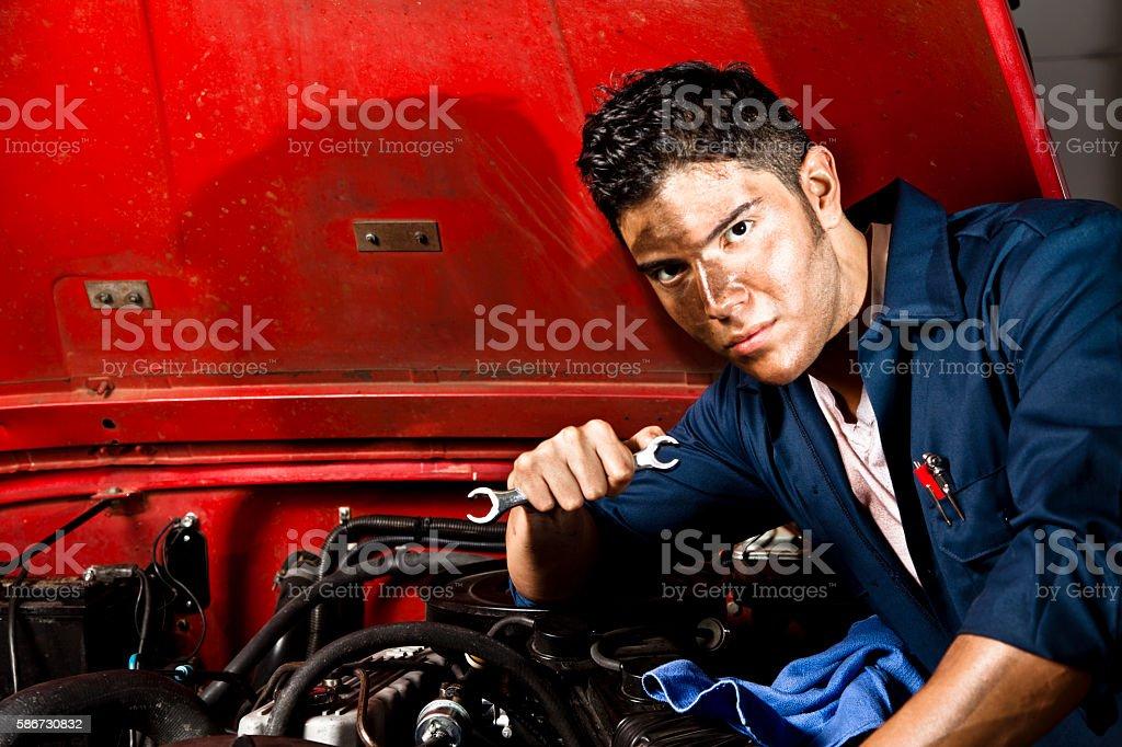 Mechanic repairs vehicle in auto repair shop. stock photo