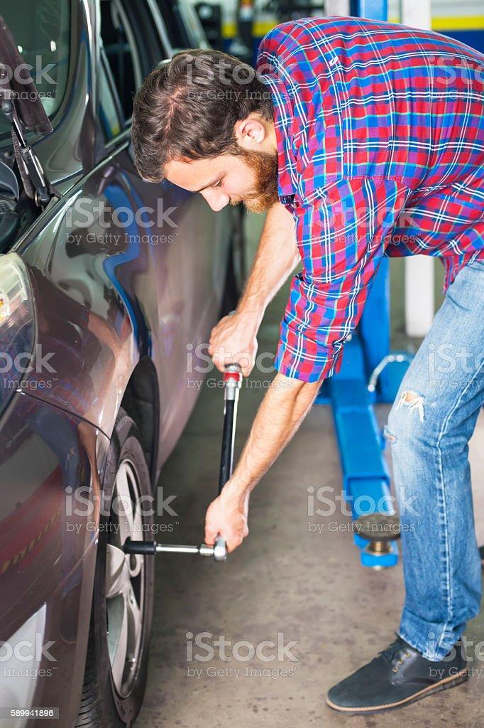 Mechanic replacing wheel stock photo