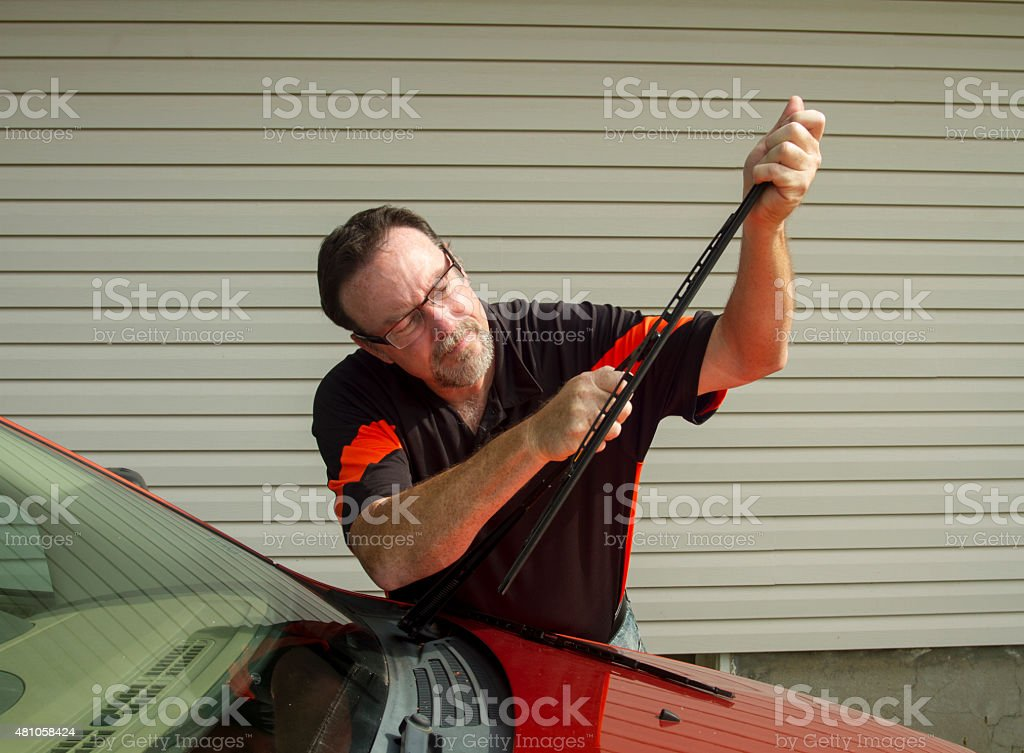 Mechanic Replacing Wiper Blades On A Car stock photo