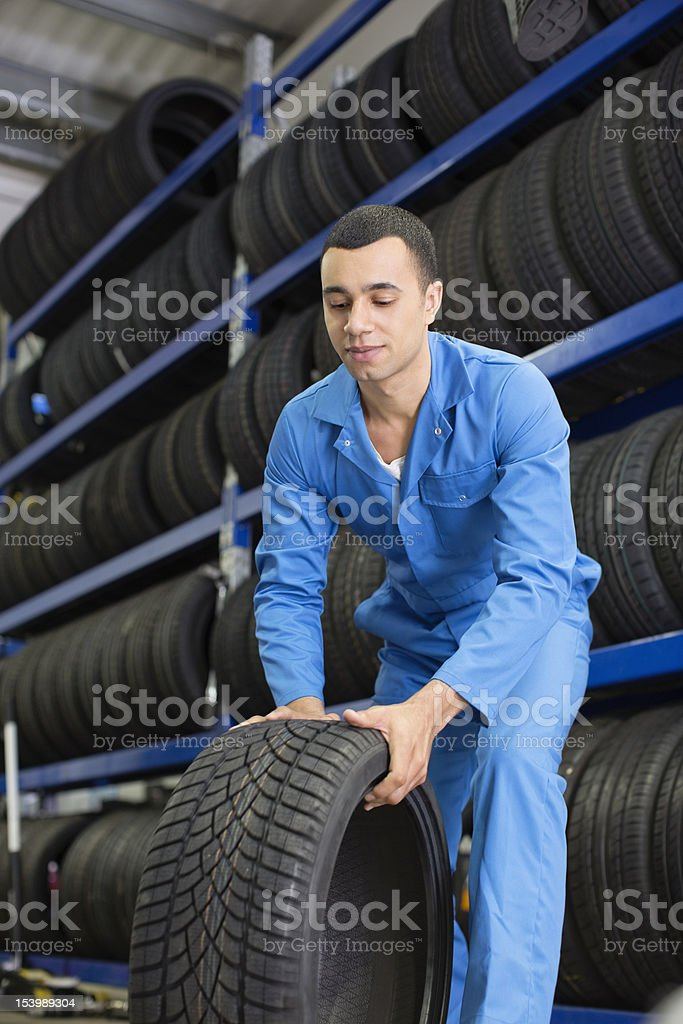 Mechanic rolling tire in auto repair shop royalty-free stock photo