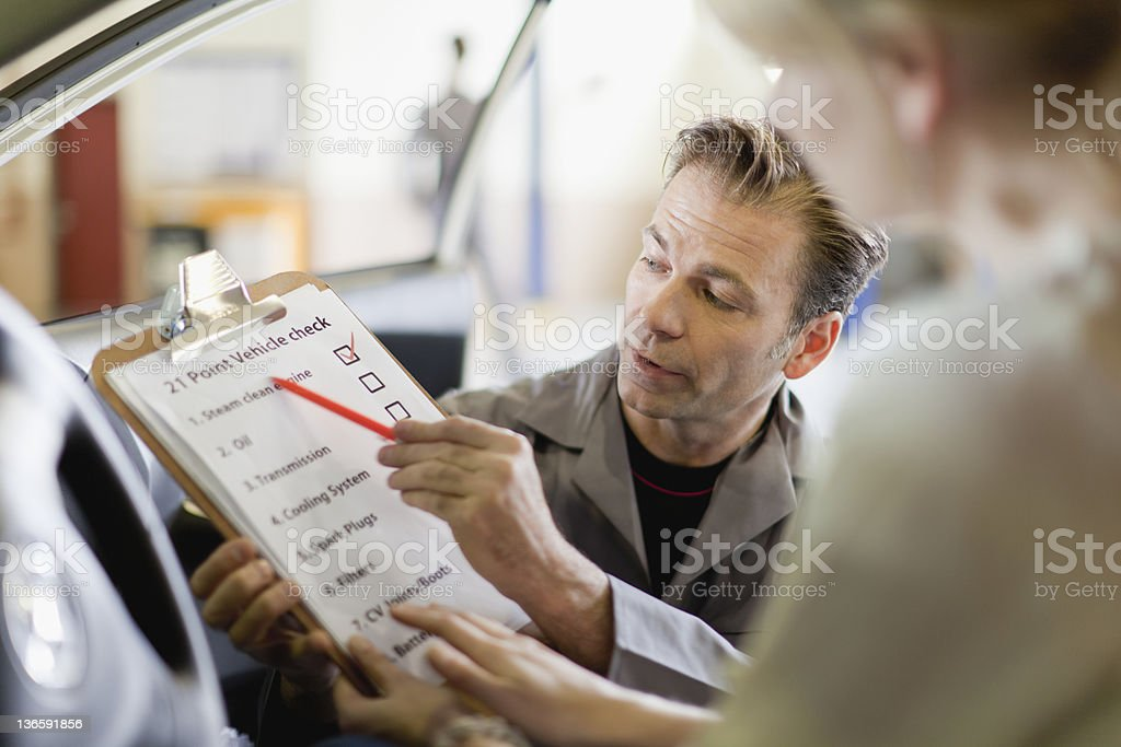 Mechanic showing checklist to customer royalty-free stock photo