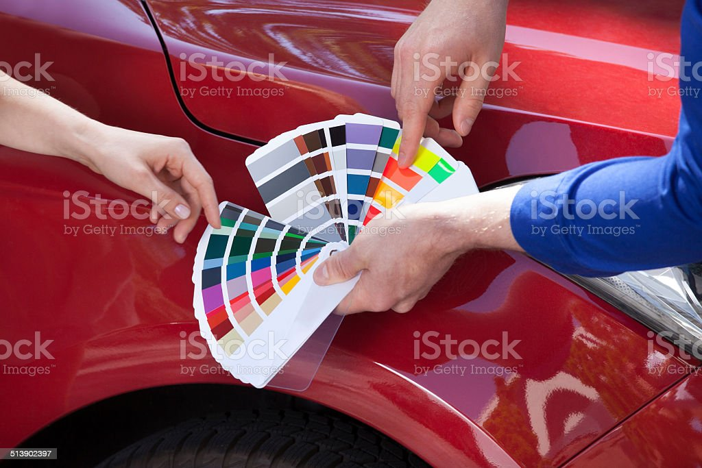 Mechanic Showing Color Samples To Customer Against Car stock photo