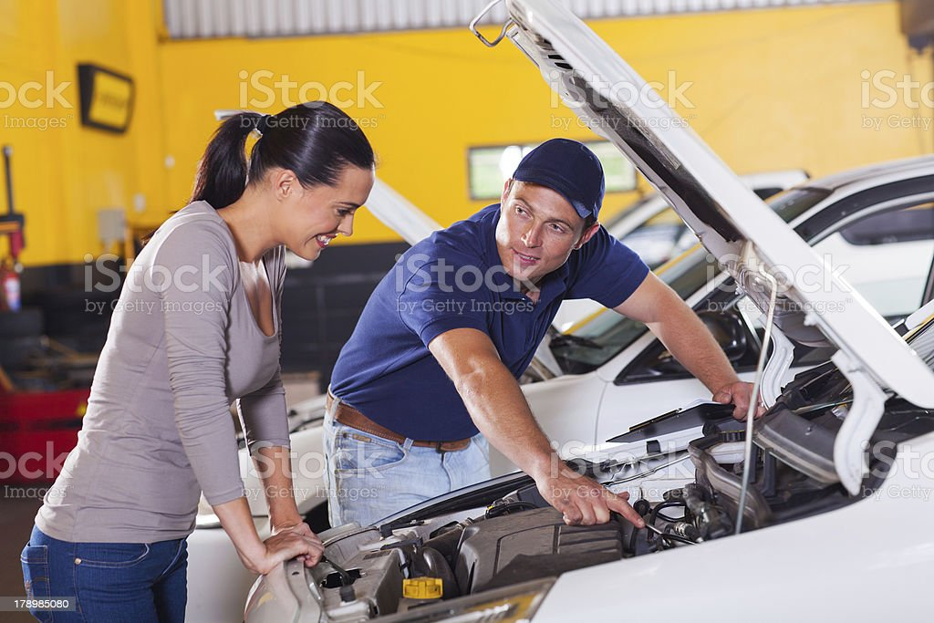 mechanic showing customer car problem royalty-free stock photo