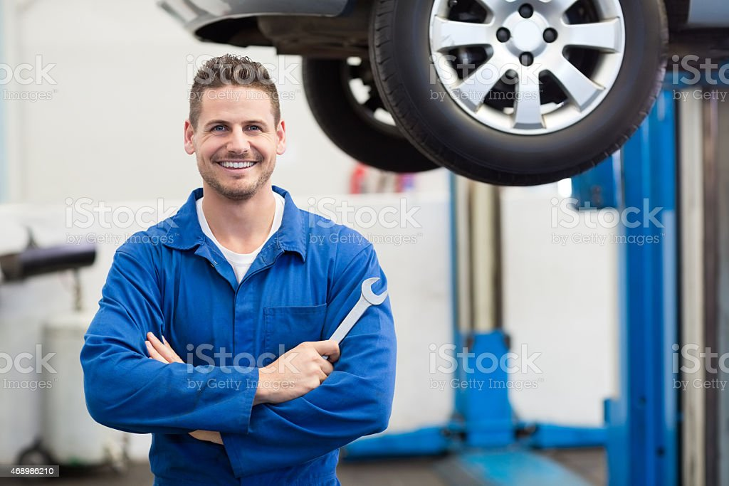 Mechanic smiling at the camera holding tool stock photo