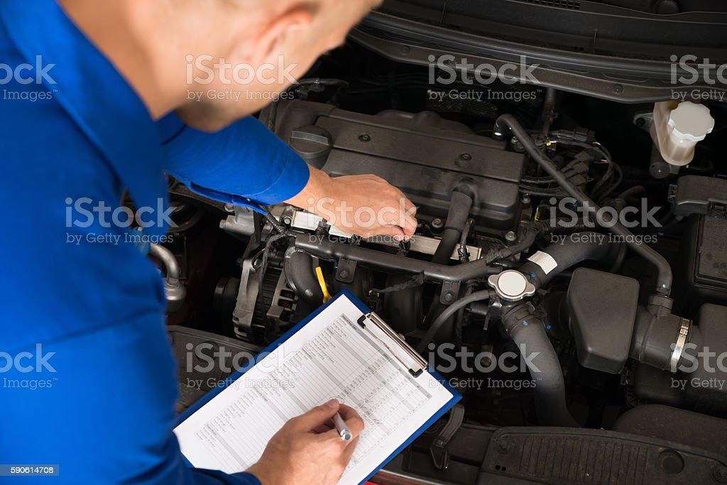 Mechanic Standing Near Car Writing On Clipboard stock photo