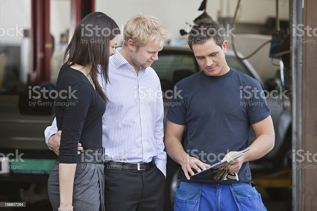 Mechanic standing with customers royalty-free stock photo
