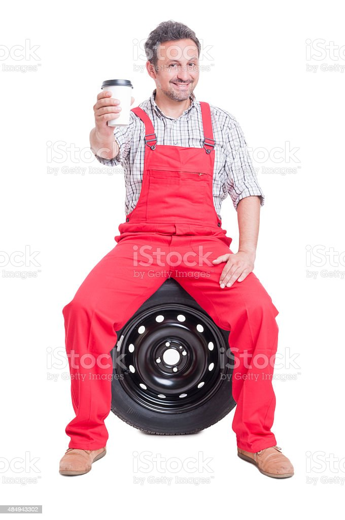 Mechanic taking a break and drinking coffee to go stock photo