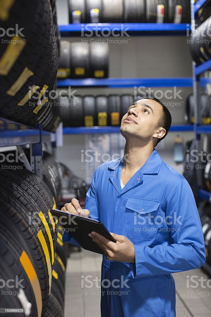 Mechanic taking inventory of tires on shelves in auto repair shop royalty-free stock photo
