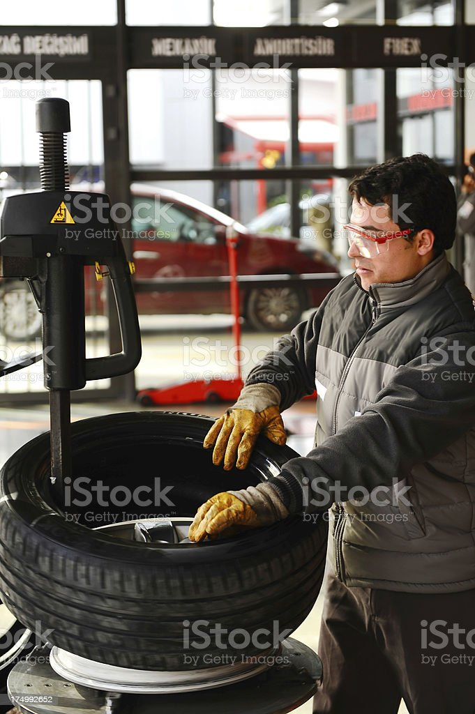 Mechanic taking off old tire royalty-free stock photo