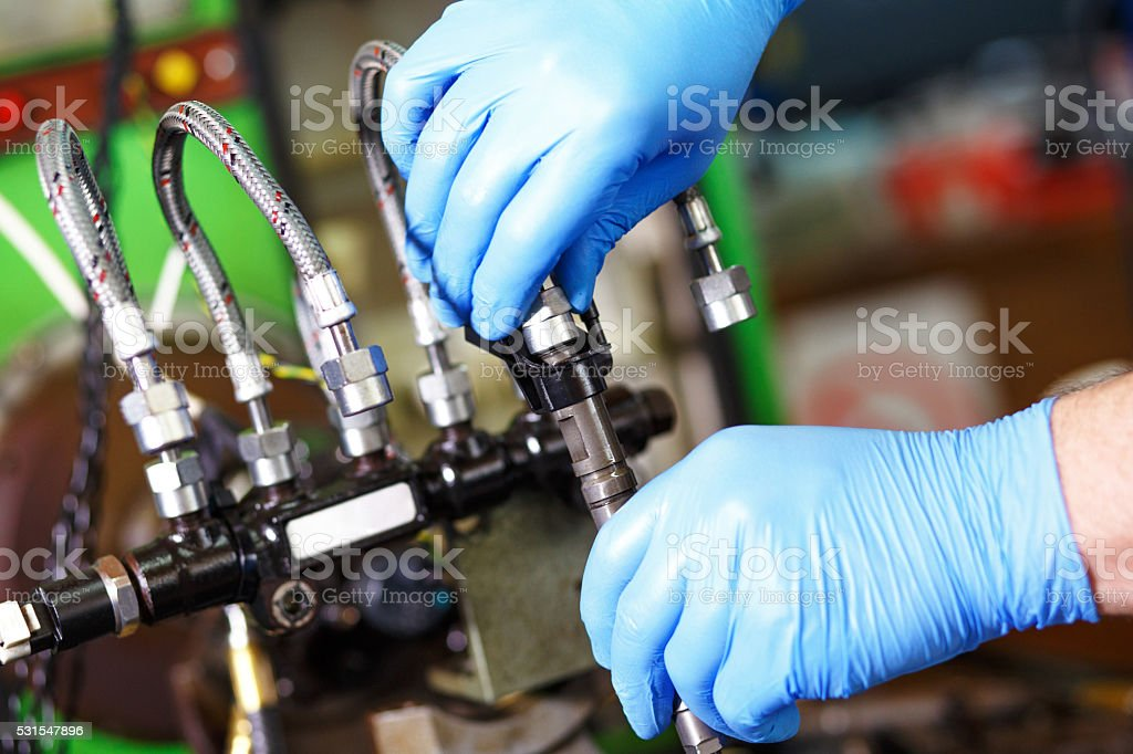 Mechanic testing diesel injector stock photo
