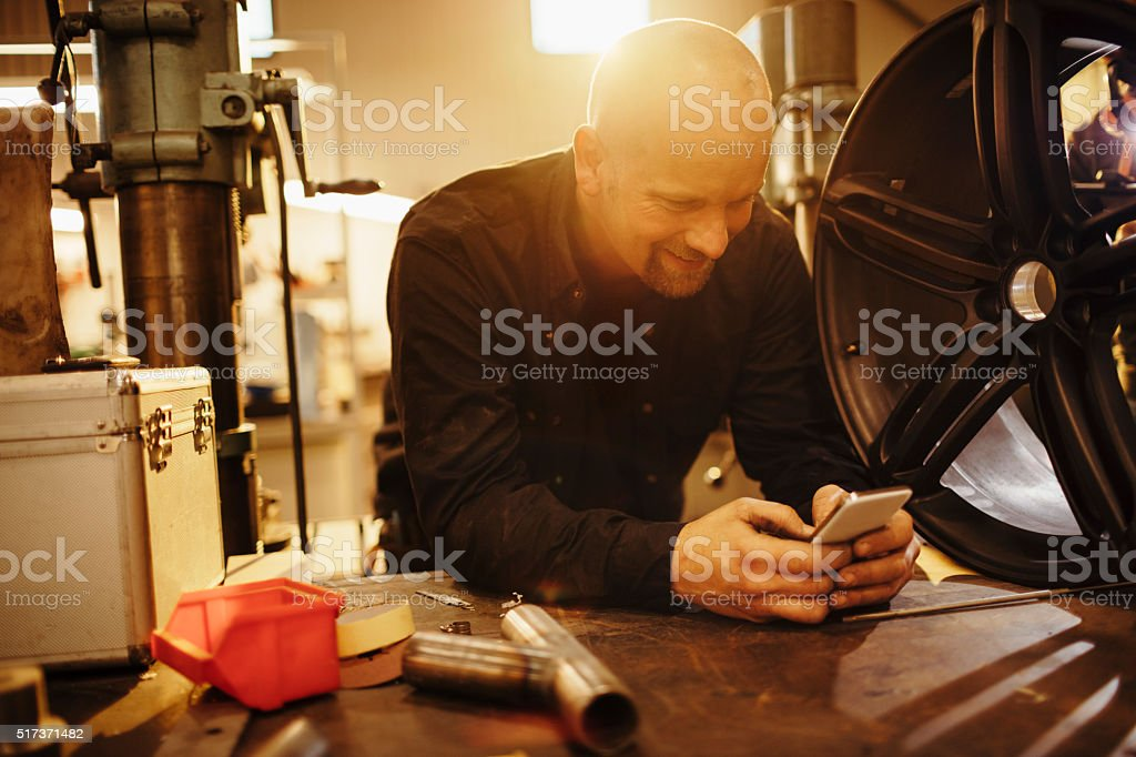 Mechanic texting while working stock photo