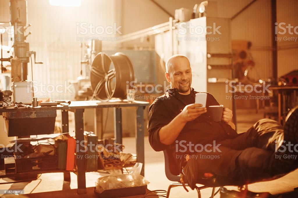 Mechanic textingl while working stock photo