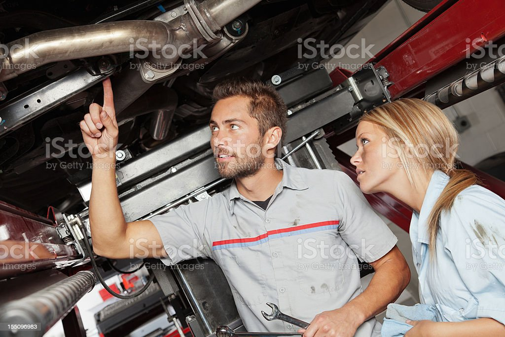 Mechanic training new trainee at auto body shop. royalty-free stock photo