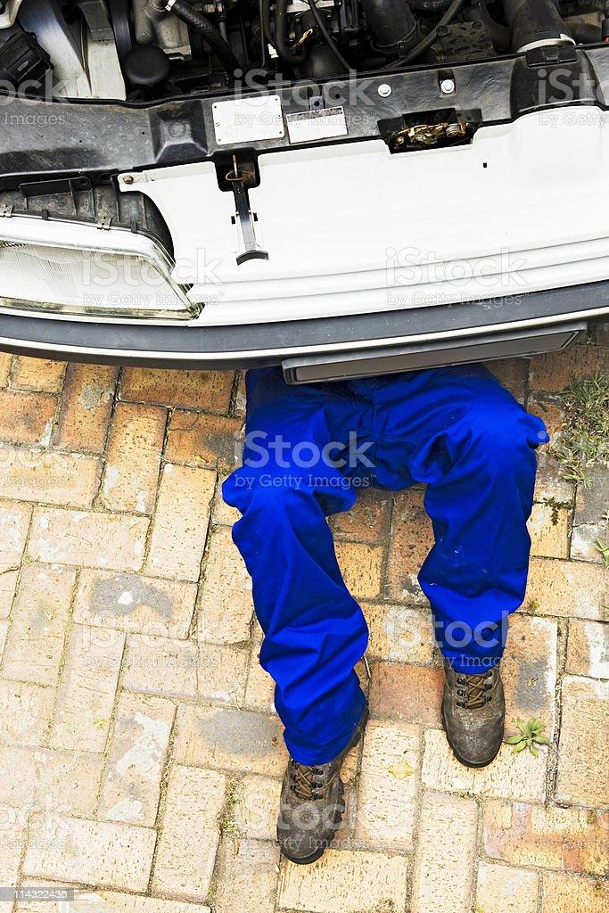 Mechanic under car stock photo