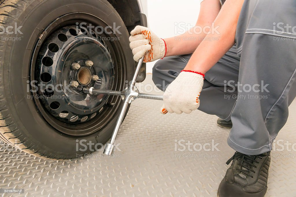 mechanic unscrews the wheel a wrench, close-up shot stock photo