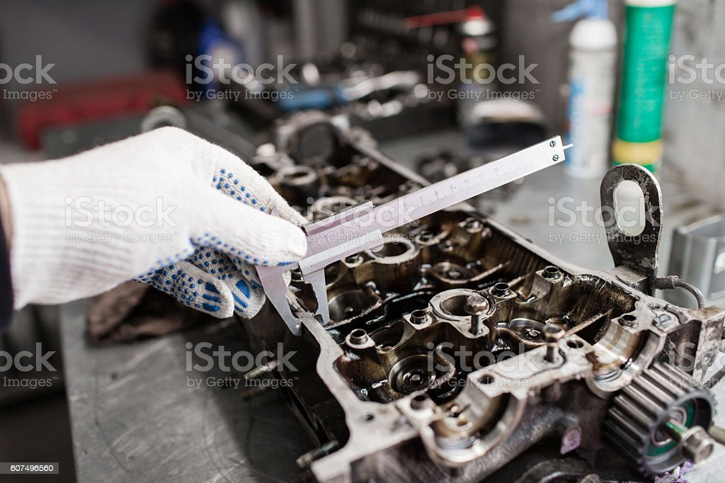 Mechanic, using a calipher, to check the thickness. Full engine stock photo