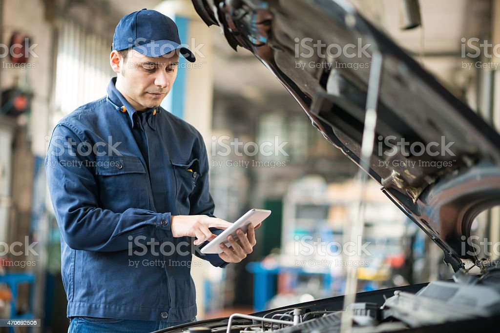 Mechanic using a tablet in his garage stock photo