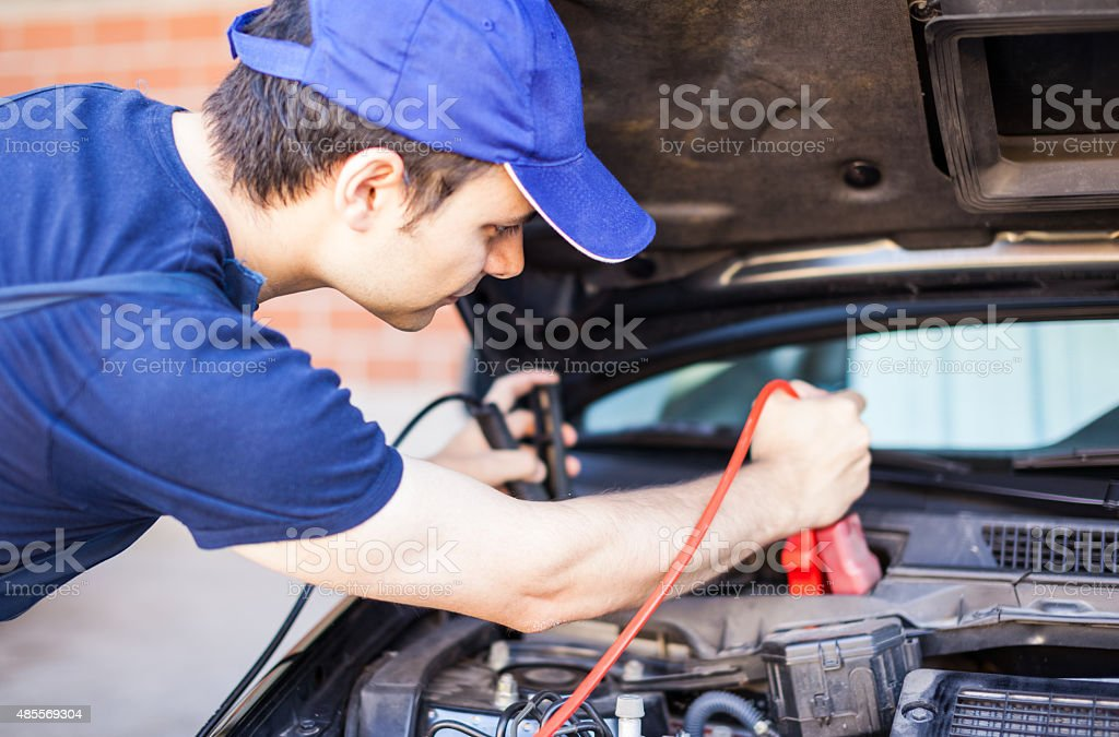 Mechanic using cables to start-up a car engine stock photo