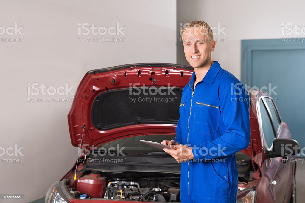 Mechanic Using Digital Tablet In Garage stock photo