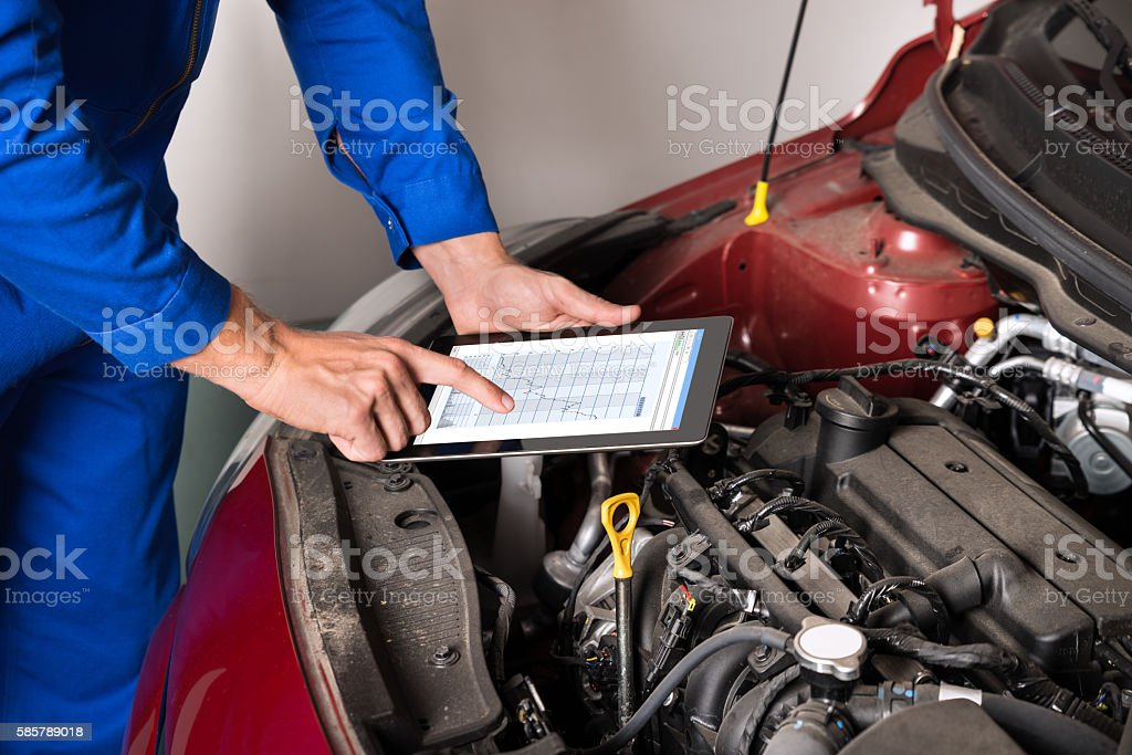 Mechanic Using Digital Tablet While Examining Car Engine stock photo