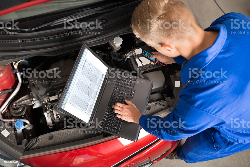 Mechanic Using Laptop To Repair Car stock photo